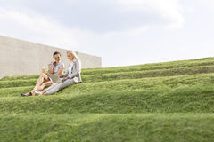 Young businesswomen using laptop together while sitting on grass steps against sky Royalty Free Stock Photo