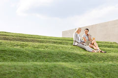 Young businesswomen using laptop together while sitting on grass steps against sky Stock Images
