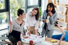Young businesswomen working with blueprint and drinking coffee in office Royalty Free Stock Images