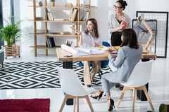 Young businesswomen working with blueprints and discussing new project. Multiethnic group of young businesswomen working with blueprints and discussing new Stock Image