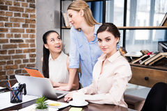 Young businesswomen working with laptop and digital tablet at workplace. Smiling young businesswomen working with laptop and digital tablet at workplace Royalty Free Stock Photos