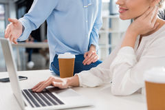 Young businesswomen working with laptop and talking in small business office Royalty Free Stock Photography