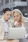 Young businesswomen working on laptop together while sitting outdoors Stock Photography
