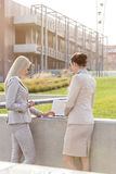 Young businesswomen working together on laptop while standing against office building Royalty Free Stock Photo