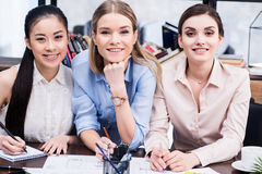 Young businesswomen working together at table and smiling at camera Stock Images