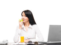 A young busineswoman eating an apple on white Royalty Free Stock Photography