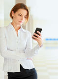 Young busineswoman standing with phone in office Royalty Free Stock Photos