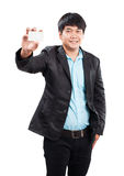 Young businss man standing with happy face holding name card in Royalty Free Stock Photography