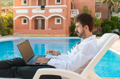 Young bussines man working on his lap top by the pool Royalty Free Stock Photo