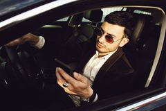 Young bussinesman in suit and black glasses speaks by phone in his car. Bussines look. Test drive of the new car.  stock photo