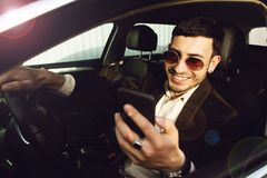 Young bussinesman in suit and black glasses speaks by phone in his car. Bussines look. Test drive of the new car.  royalty free stock photo