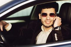 Young bussinesman in suit and black glasses speaks by phone in his car. Bussines look. Test drive of the new car.  royalty free stock photography