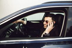 Young bussinesman in suit and black glasses speaks by phone in his car. Bussines look. Test drive of the new car.  stock image