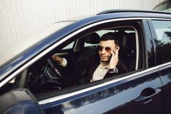 Young bussinesman in suit and black glasses speaks by phone in his car. Bussines look. Test drive of the new car.  royalty free stock photos