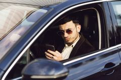 Young bussinesman in suit and black glasses speaks by phone in his car. Bussines look. Test drive of the new car.  stock photography