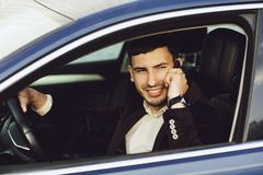 Young bussinesman in suit speaks by phone in his car. Bussines look. Test drive of the new car.  stock photo