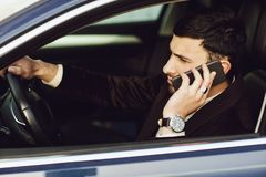Young bussinesman in suit speaks by phone in his car. Bussines look. Test drive of the new car.  royalty free stock images
