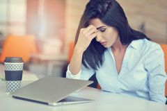 Young busy beautiful latin business woman suffering stress working at office computer royalty free stock photo