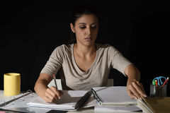 Young busy beautiful Spanish girl studying at home late night looking preparing exam concentrated. And quiet in education work and effort concept Royalty Free Stock Photos