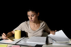 Young busy beautiful Spanish girl studying at home late night. Looking preparing exam concentrated and quiet in education work and effort concept Royalty Free Stock Image