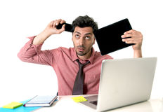 Young busy businessman at office desk working with mobile phone digital tablet and computer laptop looking crazy desperate Stock Photography