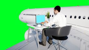 Young busy businessman working on the flying plane. African male looking into the screen of the laptop on the desk. Creative workspace concept. 3d rendering Stock Photos