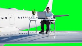 Young busy businessman working on the flying plane. African male looking into the screen of the laptop on the desk. Creative workspace concept. 3d rendering Stock Photo