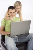 Young busy couple with laptop Royalty Free Stock Image