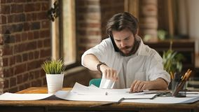 Young Busy Designer. Handsome bearded busy designer working at table workplace, drawings on papers while talking via phone in loft studio stock video