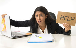 Young busy desperate Latin businesswoman holding help sign sitting at office desk in stress worried Royalty Free Stock Image