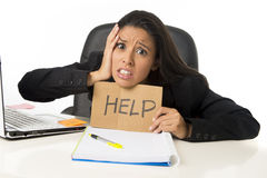 Young busy desperate Latin businesswoman holding help sign sitting at office desk in stress worried Stock Photo