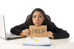 Young busy desperate Latin businesswoman holding help sign sitting at office desk in stress worried Royalty Free Stock Photos