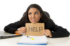 Young busy desperate Latin businesswoman holding help sign sitting at office desk in stress worried Stock Image