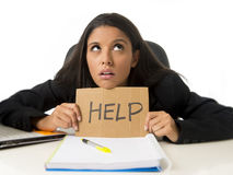 Young busy desperate Latin businesswoman holding help sign sitting at office desk in stress worried Stock Photography