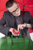 Young busy man. With red umbrella checking time Stock Photo