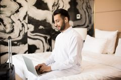 Guy typing. Young busy man with earphones and laptop sitting on bed and typing in hotel room or at home royalty free stock image