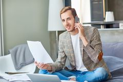 Home consulting. Young busy man with papers talking by smartphone while sitting on bed at home royalty free stock image