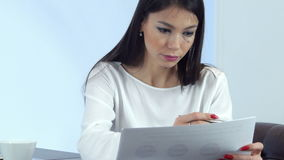 Young busy woman preparing report and making notes sitting in the cafe stock footage