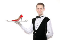 Young butler holding a tray with a high heel on it. Isolated on white stock image