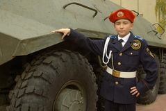 Young cadet with an armored troop carrier. Young cadet standing near an armored troop carrier Stock Image