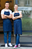 Young cafe owners in doorway. Smiling stock image