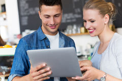 Young cafe owners looking at laptop Stock Photography