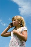 Young call. Young girl talking on cell phone with sky background Royalty Free Stock Images