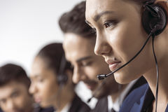 Young call center operator in headset working with colleagues stock photo