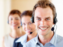 Young call centre guy with colleagues at the back Royalty Free Stock Image