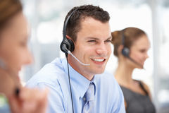 Young call centre operator helping customer. At work Stock Photography