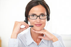 Young callcenter employee talking on headphones Stock Photos