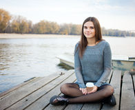 Young calm beautful brunette woman with coffee outdoors Stock Photo