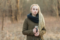 Young calm beautiful blonde hipster woman posing with thermos cup cold season outdoors Stock Photos