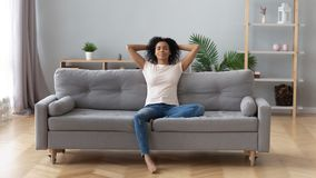 Calm black woman relaxing on comfortable sofa in living room